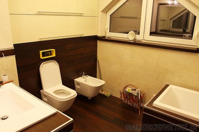 Łazienka z ciemnymi panelami Quick Step Laguna i jasnymi beżowymi płytkami na ścianie. ...