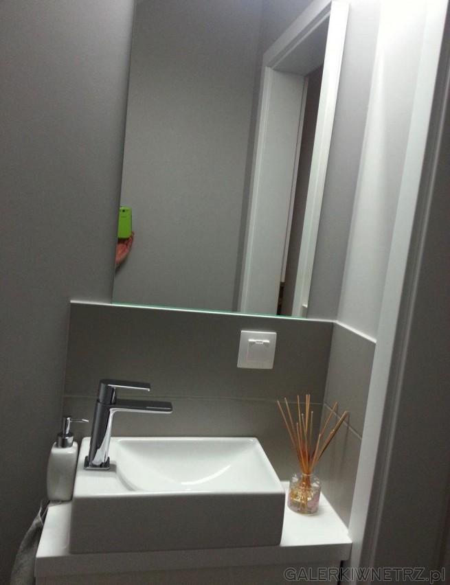 W tej niewielkiej toalecie znajduje się umywalka o prostokątnym kształcie oraz bateria ...