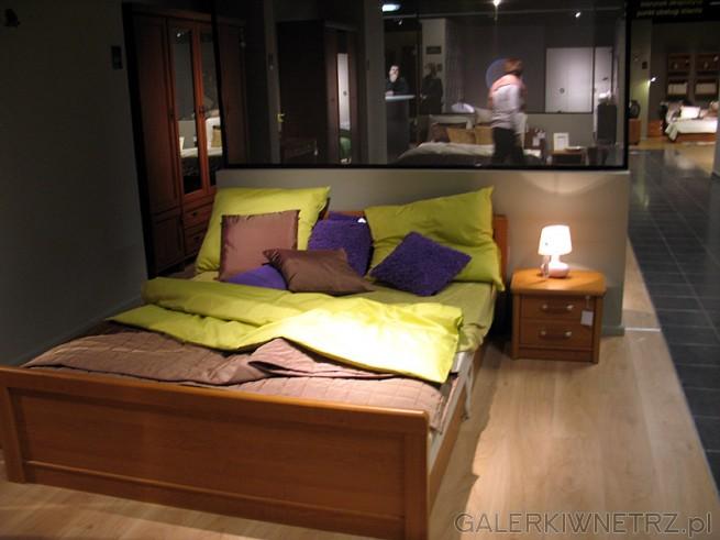 Łóżko dwuosobowe wykonane z dośćciemnego drewna, o prostym kształcie, całość dopełnia ...