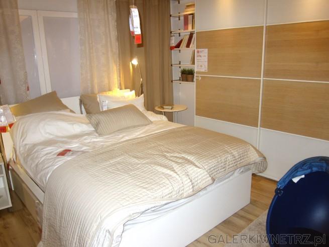 Aranżacja sypialni z łóżkiem dwuosobowym, z białą, prostą ramąłóżkową. W sypialni ...