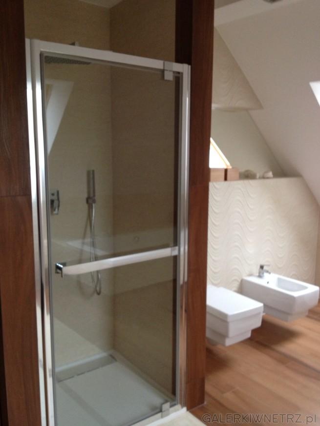 Prysznic jest na basie prostokąta, ma przezroczyste drzwi w lekko posrebrzanej obudowie. ...