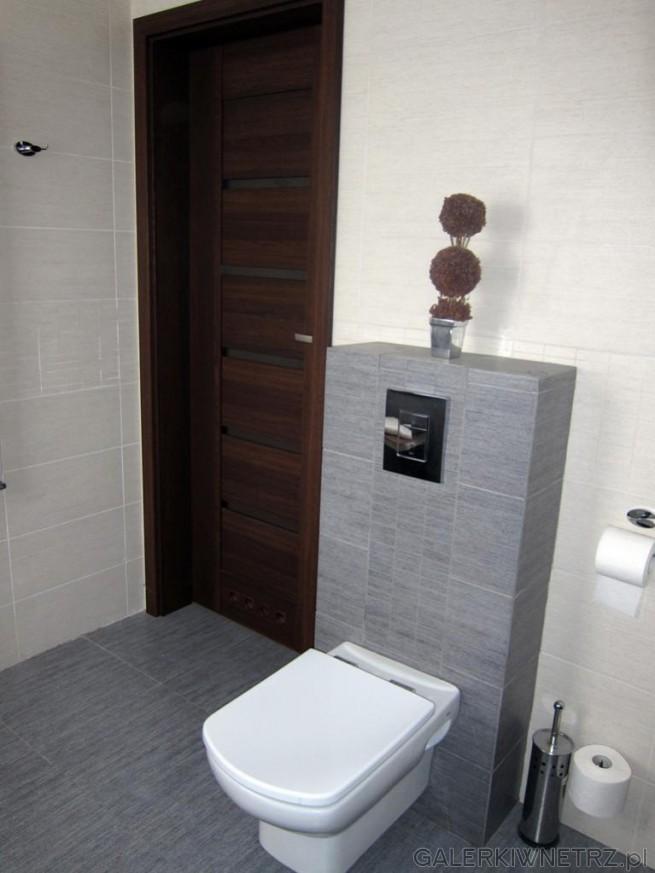 Prostokątna misa WC wisząca zawieszona jest na nieco wysuniętej ściance obudowanej ...