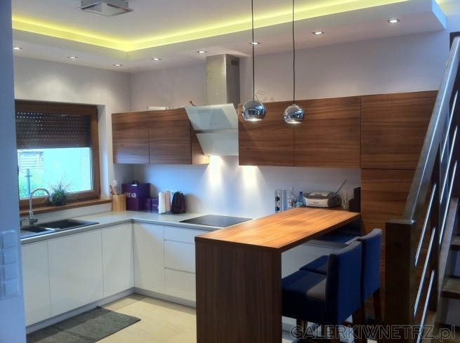 Biało-brązowa kuchnia z fioletowymi dodatkami. Oświetlenie sufitowe oraz zwisające ...