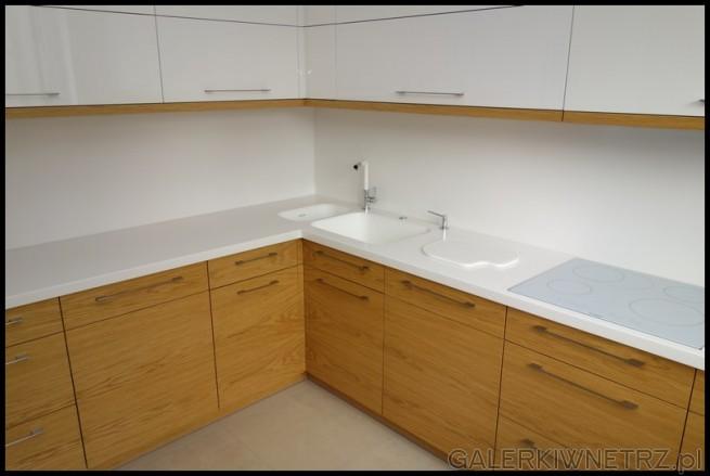 Projekt kuchni z wykorzystaniem białych i drewnianych szafek. Na białym blacie znajduje ...
