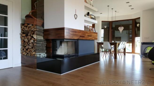 Kominek, wykonany w bieli i czerni z elementem drewna znajduje siępomiędzy salonem ...
