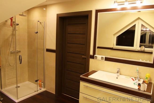 Ładna aranżacja łazienki w beżach i brązach. Pod prostokątną umywalkąznajdują siępółki ...