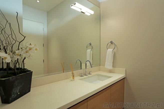 Elegancka, prosta łazienka w bieli i w drewnie. Pod jedną ze ścian przychodzi biały ...