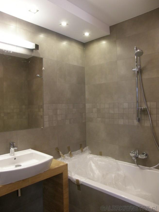 Nad ścianą, przy której znajduje sięlustro i umywalka pod sufitem zainstalowane ...