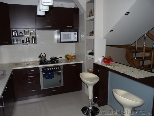 Kuchnia w domu jednorodzinnym. Ciemne szafki kuchenne. Ciekawa zabudowa zwykłej ...