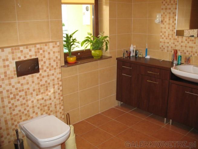 Łazienka z oknem, beżowe kafle, podwieszany WC
