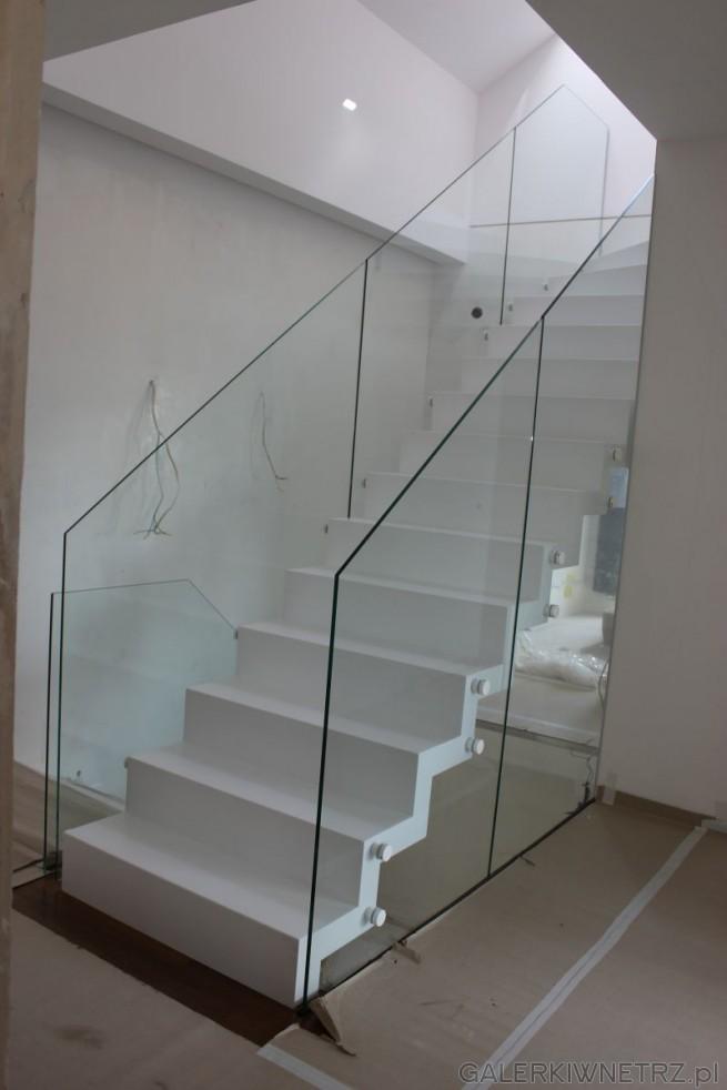 Białe schody z dwóch stron ograniczone szklanymi balustradami o ostrym zakończeniu. ...
