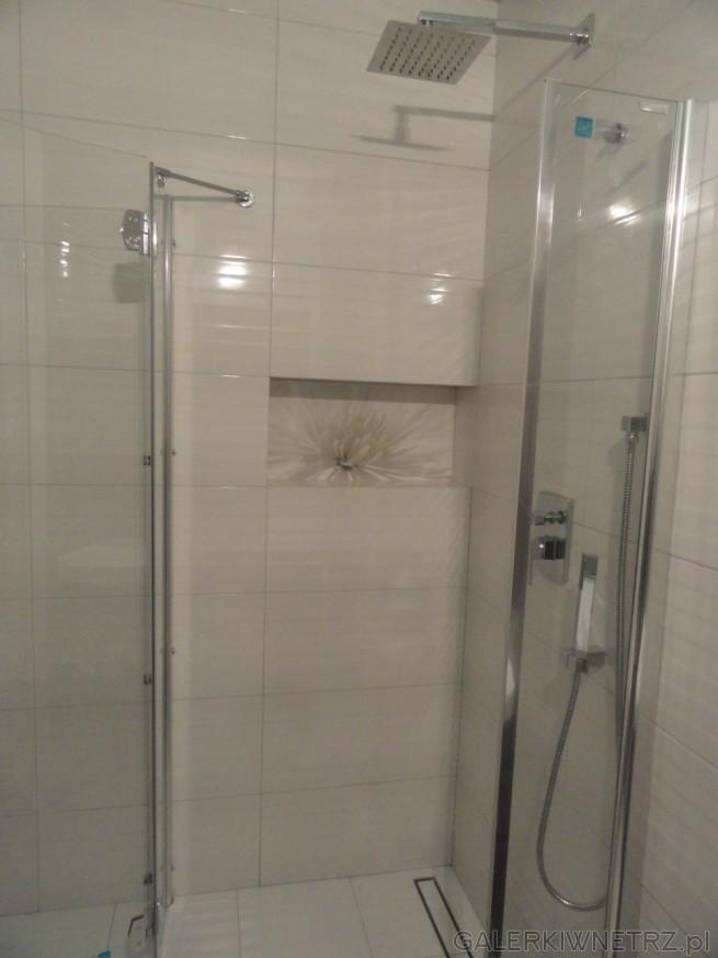 Pod prysznicem ściany wyłożone są aż do sufitu białą glazurą, lekko przełamaną kolorem ...