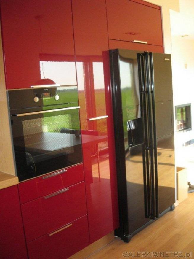 Czerwone meble,przełamane czarnymi elementami, jak piekarnik, czy lodówka