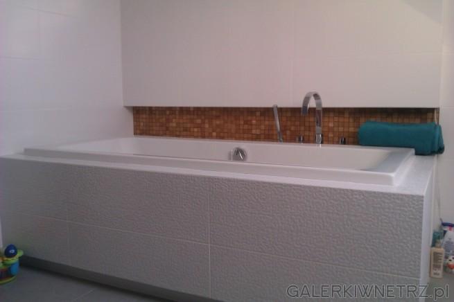 Schludna, ładna łazienka utrzymana w bieli. Wanna jest obudowana białymi płytkami ...