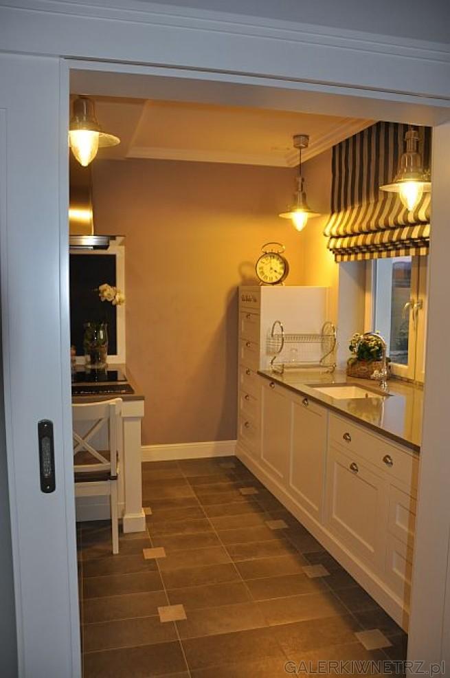 Aranżacja stonowanej kuchni w szarościach i bieli. Na suficie podwieszone są lampy ...