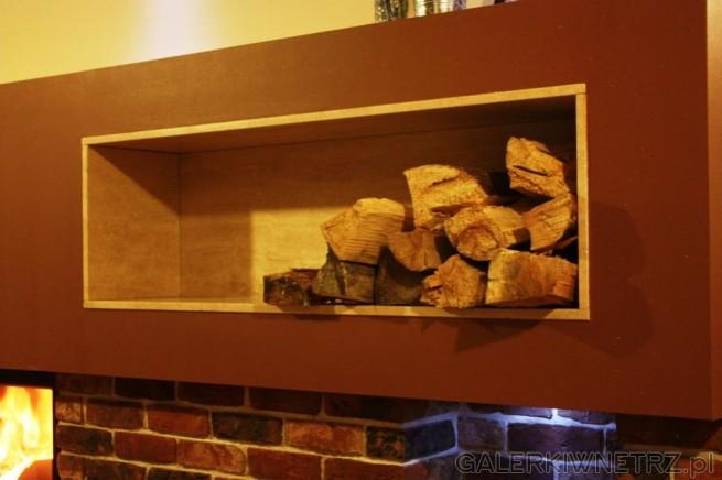 Zbliżenie na wnękę na drewno. Wnęka została wykonana z trawertynu, natomiast zabudowana ...