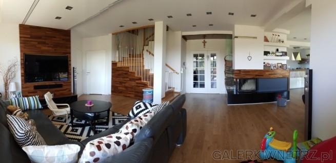 Półotwarty salon graniczący ze schodami a także z kuchnią. Czarna kanapa o kształcie ...