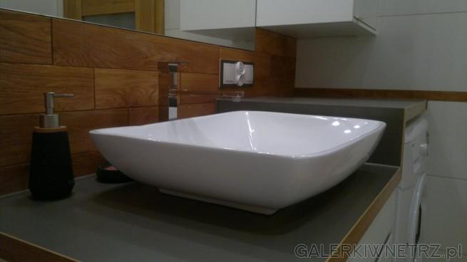 Ładna umywalka, dość płytka i o kształcie zbliżonym do prostokąta. Stoi ona na blacie, ...