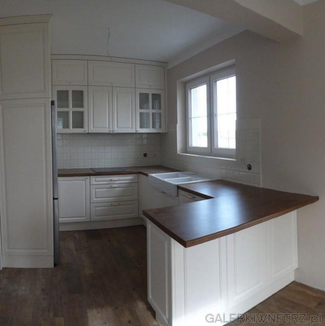 Przyjemny projekt kuchni w bieli i w drewnie. Jest to kuchnia półotwarta, stylizowana ...