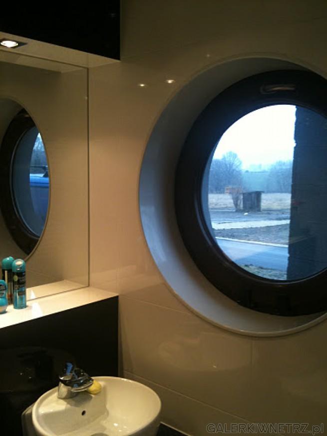 Małe, okrągłe okienko wykonane z listwy ze stali szlachetnej, pomalowane na biało. ...