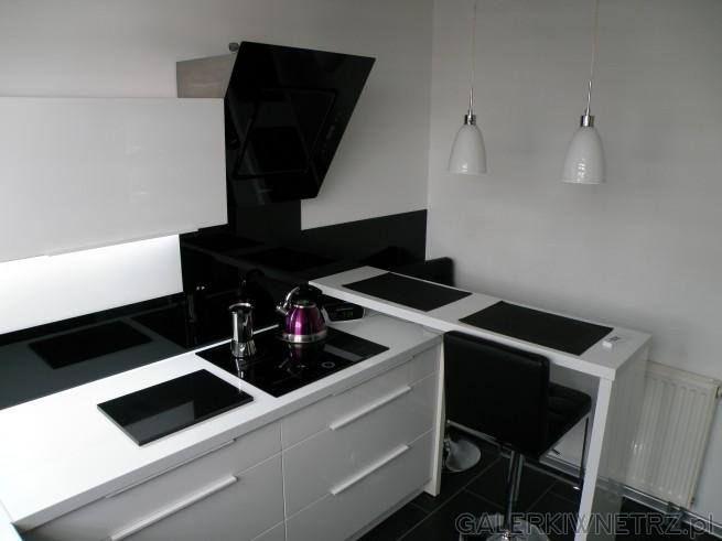 Aranżacja niewielkiej kuchni w bieli i czerni. Ściany pomalowane są na biało. W ...