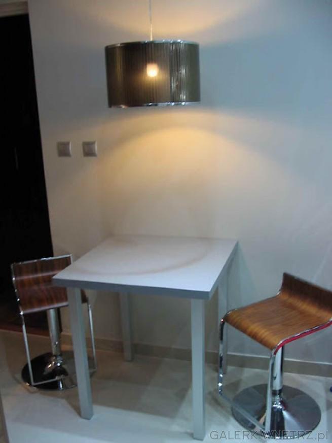 Mały stolik z dwoma krzesłami-prowizoryczna jadalnia.Na podłodze Szkliwione Płytki ...