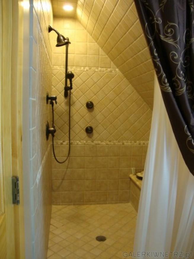 Czarna armatura firmy Delta w skrajnej części łazienki ze skosem służącej za prysznic. ...