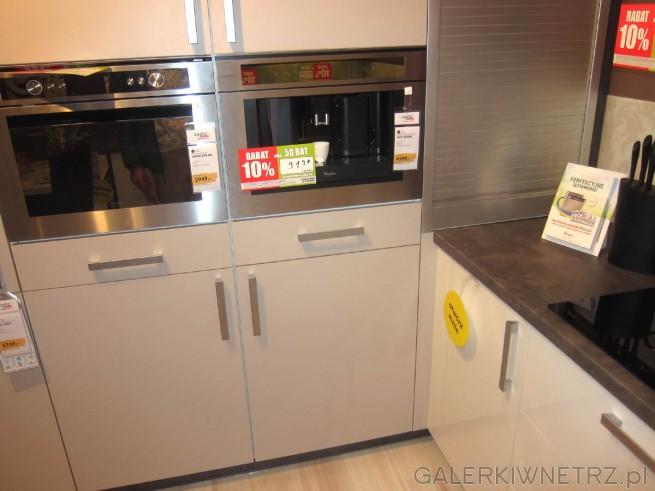 W słupku pomiędzy szufladami i szafkami umieszczono sprzęt AGD (piekarnik oraz ekspres ...