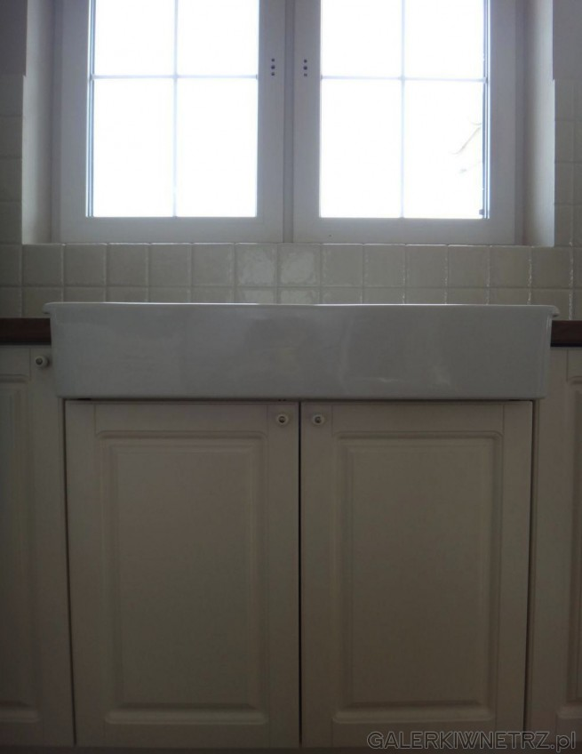 Duży zlew z dwoma komorami został umieszczony na szafce z dwoma drzwiczkami, nad ...