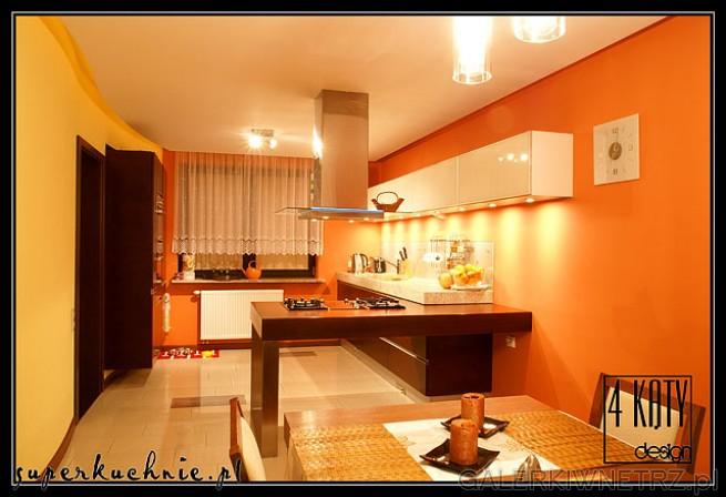 Kuchnia połączona z jadalnią w ciepłej, witalizującej kolorystyce. Zastosowane na ...