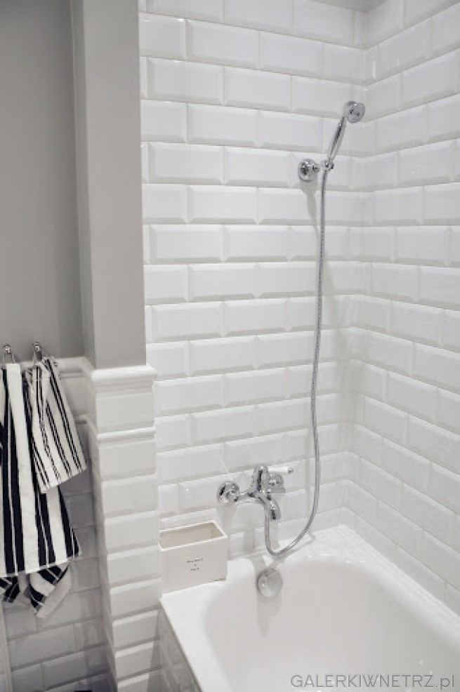 Mała łazienka urządzona całkowicie w bieli i szarości. Łazienka ta ma wygląd nieco ...