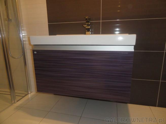 Prostokątna umywalka podblatowa położona została na ciemnej szafce, której front ...