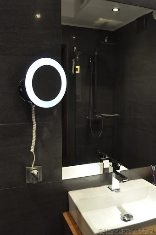 Kwadratowa umywalka w białym kolorze, do tego duże lustro bez ramy oraz małe powiększające ...
