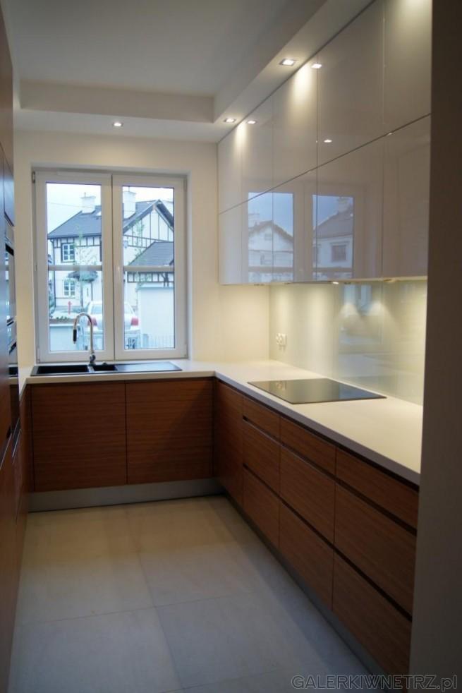 Aranżacja bardzo wąskiej kuchni w bieli i w brązie. Fronty kuchenne sąbiałe, połyskujące, ...