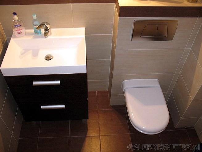 WC typu Geberit i srebrny klawisz. Brązowa szafka wraz z umywalką. Chromowane uchwyty ...