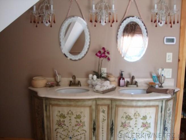 Podwójna umywalka, dwa owalne lustra oraz złote baterie. Oświetlanie w postaci małych ...