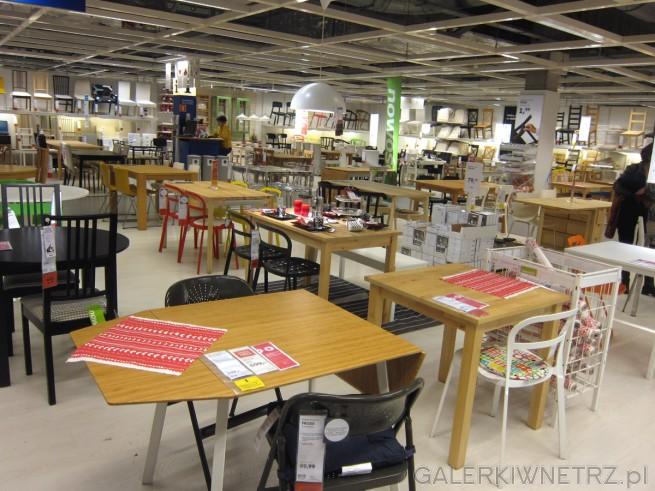 Drewniany stolik z rozkładanymi częściami, tworzący ciekawy kształt. Różne krzesła, ...