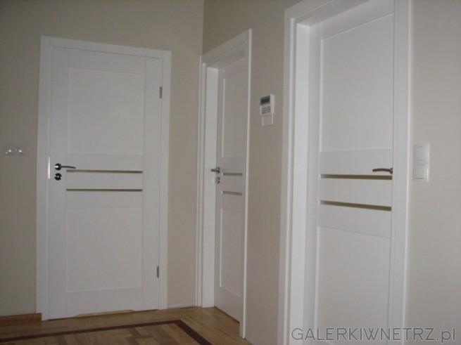 Białe drzwi wewnętrzne marki Porta. Drzwi mająprostą formę. Pośrodku względem wysokości ...