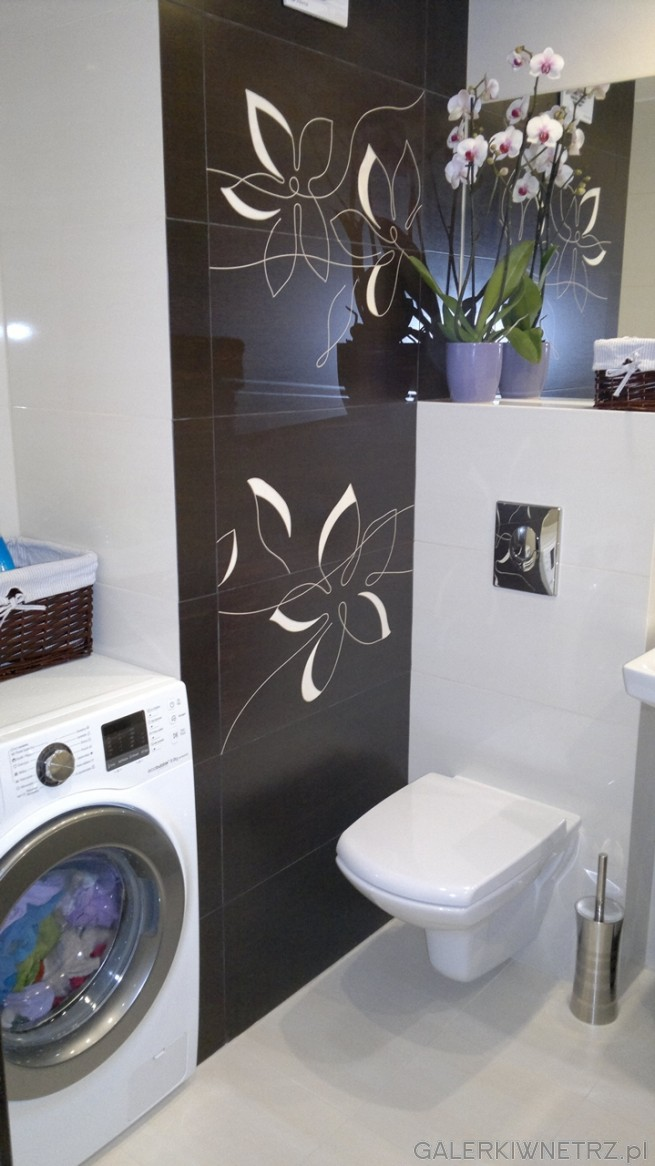 Czarny dekor Paradyż z motywem białych kwiatów dodaje elegancji tej łazience. Wnękę ...