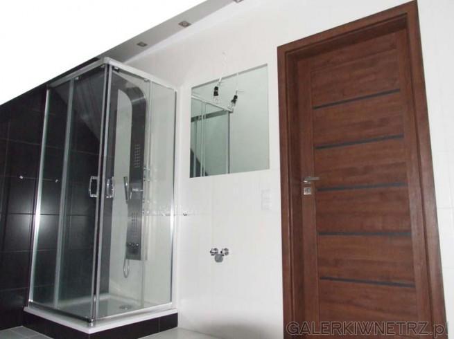 Ciemnobrązowe drzwi, pasujące do okienka. Kwadratowy prysznic z odsuwaną kabiną. ...