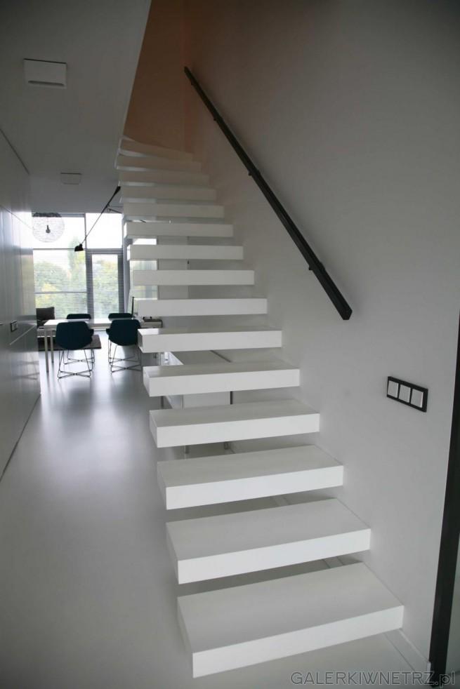 Białe schody wspornikowe dla lubiących minimalizm. Stopnie są białe, dośćgrube, ...