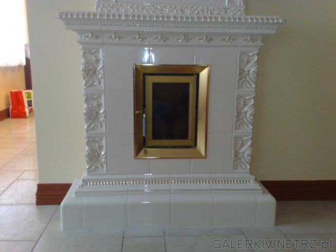 Detal na złocone palenisko, które jest pionowe i symetryczne względem całego kominka. ...