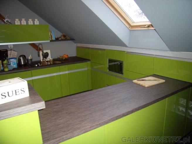 Ściana pod skośnym dachem jest zabudowana zielonymi szafkami - pomiędzy nimi znajduje ...