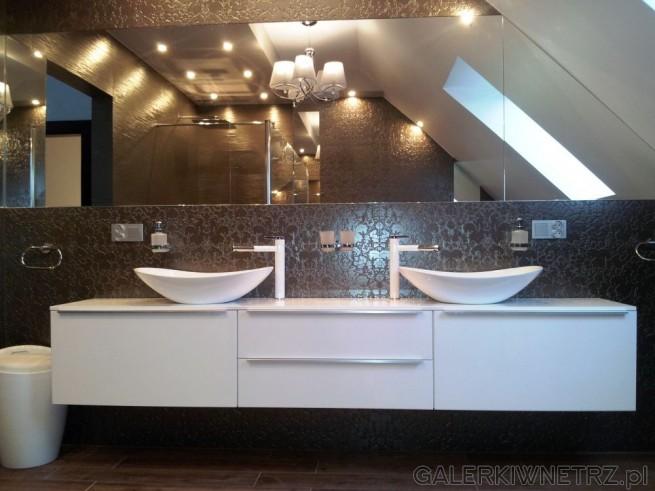 Aranżacja łazienki z ciemnymi płytkami oraz białymi meblami. Na ścianie, przy której ...