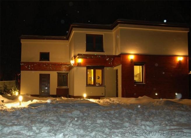 Dom jasnobeżowy z drewnianymi elementami oświetlony nocą. Większa część elewacji ...
