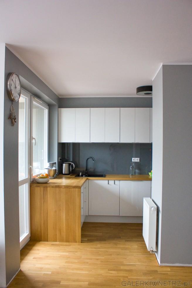 Elegancka, ponadczasowa kuchnia w bieli, szarościach i drewnie. Kuchnia jest półotwarta. ...