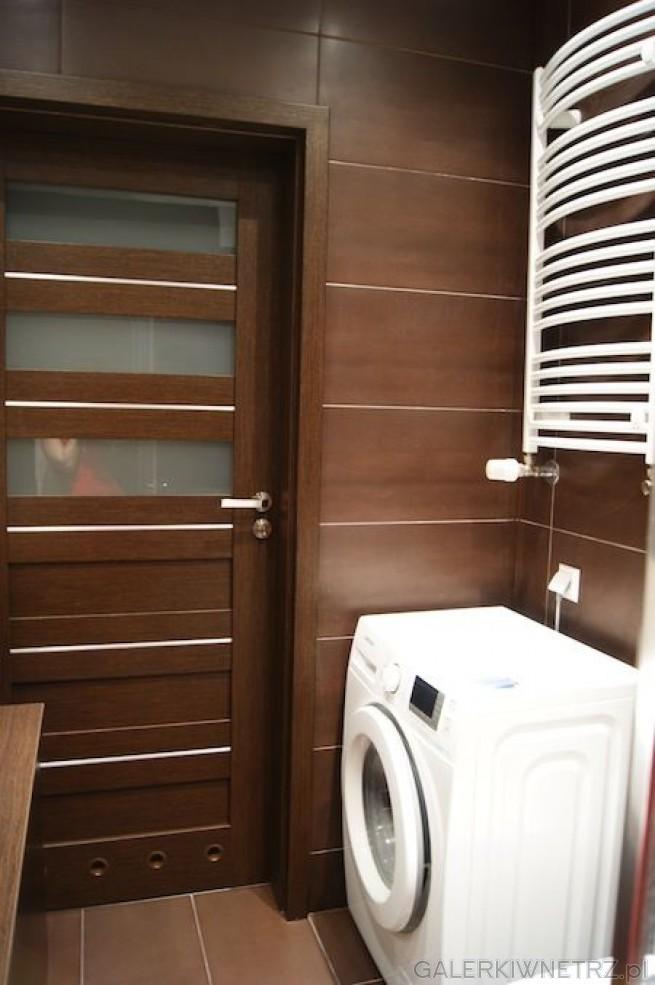 Niewielka łazienka w brązach z dużymi brązowymi płytkami na ścianie. Drzwi w tej ...