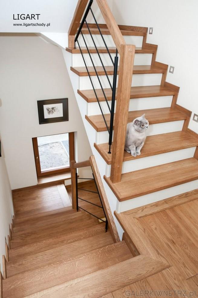 Klasyczne schody zabudowane, dwubiegowe. W ich skład wchodzi biel, drewno i metalowa ...