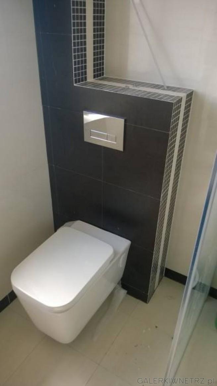 Łazienka z ciemnymi płytkami. Misa wc podwieszana na ściance wyłożonej ciemnymi ...
