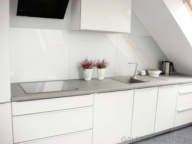 Aranżacja bardzo stonowanej, spokojnej kuchni w bieli i szarościach. Na szarym blacie ...